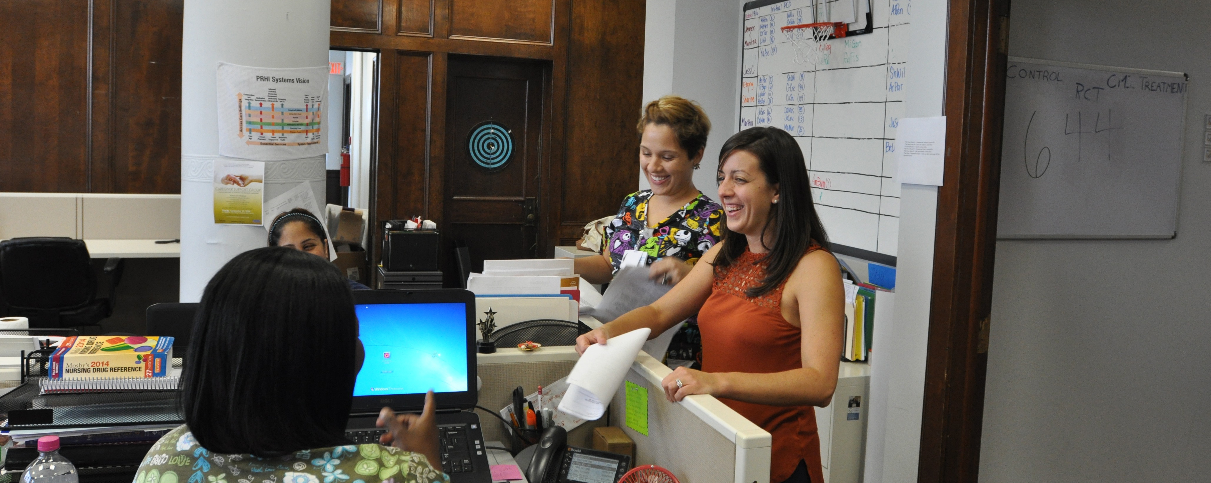 Kim McGuinness laughing with care team members in the Camden Coalition offices
