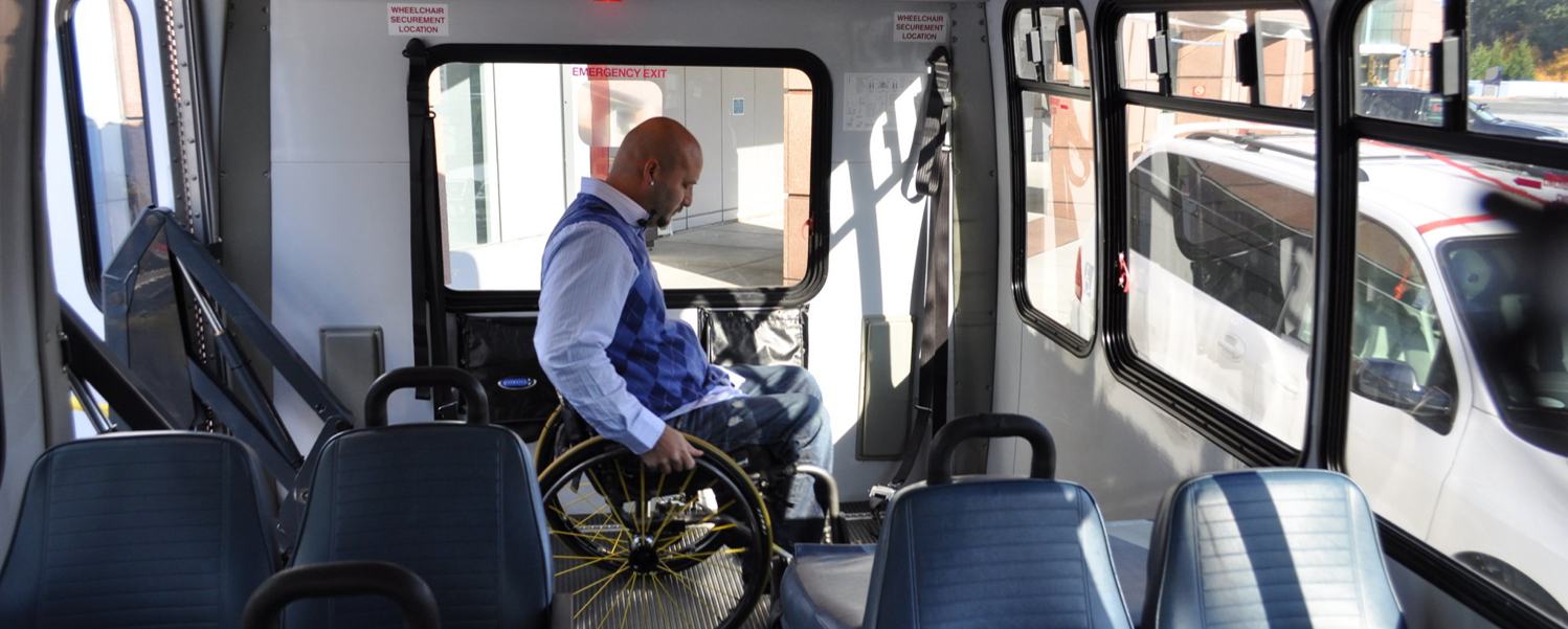 Patient in wheelchair in non-emergency medical transportation bus waits to get off bus