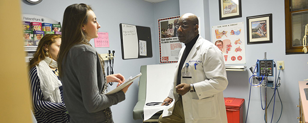 Two Camden Coalition staff members meeting with a Camden doctor at his clinic