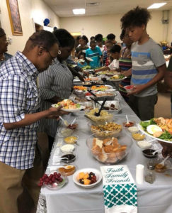 Congregants of St. John's Church of the Apostolic Faith gather for dinner