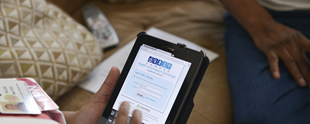 Staff member logging into Camden Coalition Health Information Exchange on a tablet at a meeting with a participant