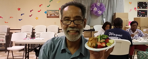 Man holds up a small plate of fruit and vegetable salad at a church dinner