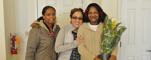 Housing First program participant holding flowers and smiling with Camden Coalition care team member in her new home