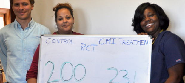 Camden Coalition staff hold whiteboard showing RCT enrollment numbers