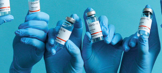Gloved hands holding vaccine vials