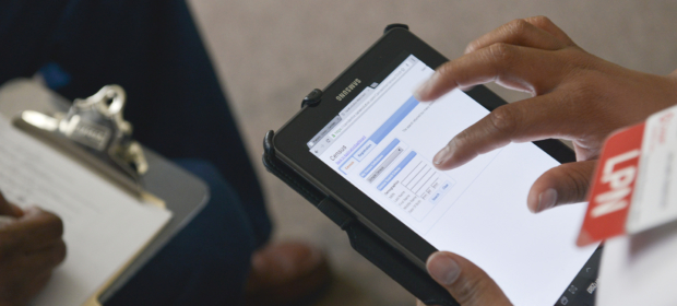 An LPN fills in information on a tablet while another individual writes on a clipboard